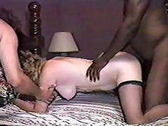 Curly haired mature babe handling two cocks at the same time